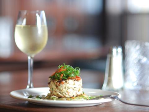 ニューオーリンズのレストランで提供される美しい盛り付けの料理とグラスワイン