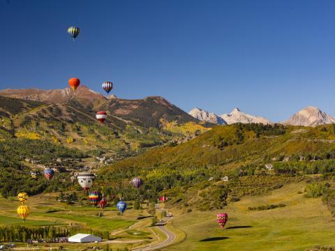 コロラド州のスノーマス・バルーン・フェスティバルで眼下の景色を見ながら浮かぶ熱気球